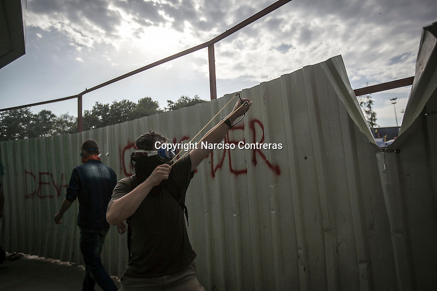 In this Tusday, Jun. 11, 2013 photo, a protester throws a stone with a slingshot to the anti-riot police duriing clashes at the streets of Taksim Square in Istanbul,Turkey. (Photo/Narciso Contreras).