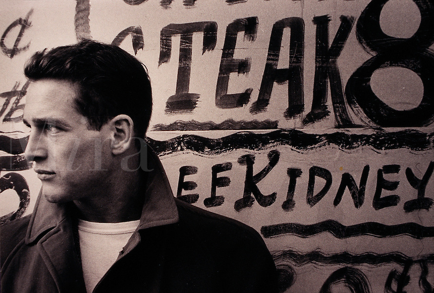 Profile portrait of actor Paul Newman in front of a sign for a butcher shop. Circa 1956.