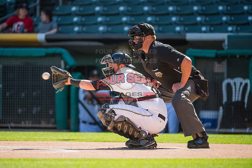 Salt Lake Bees catcher Jett Bandy (27) warms up his pitcher as home plate umpire Tom Woodring looks on during the game against the Albuquerque Isotopes in Pacific Coast League action at Smith's Ballpark on June 8, 2015 in Salt Lake City, Utah.  (Stephen Smith/Four Seam Images)