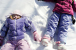 14 February 2007--Winter Storm weather Wednesday. Sarah Johnson, left, 5,and her sister Grace, 5, make snow angels in the side yard of their Marion home. PHOTO/Daniel Johnson