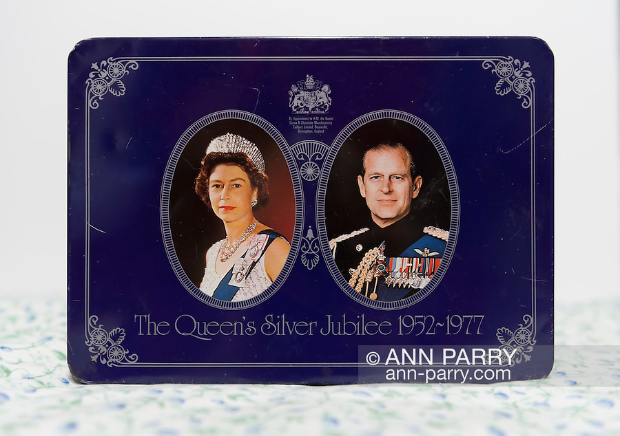 Queen's Silver Jubilee 1952-1977 Commemorative Box by Cadbury, upright on light fabric. On front: Oval pictures of Queen Elizabeth II and Prince Phillip. By appointment to H.M. the Queen, Cocoa & Chocolate Manufacturers Cadbury Limited, Bournville, Birmingham, England. Limited, Bournville, Birmingham, UK. On bottom of tin (not seen): MILK TRAY An assortment of Milk Chocolates, containing vegetable fat. Milk solids 20% minimum. NOTE: some scratches on box from usage