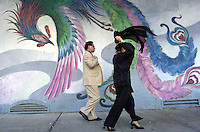 PICO VAN HOUTRYVE/Examiner 3/18/01 news.James and Elain Shen hurry along Walter U. Lum Place, the western border of Portsmouth Square, in San Francisco's Chinatown, Sunday, March 18, 2001. Mrs. Shen is putting on her shawl as they walk past the mural of a phoenix.
