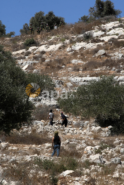 Palestinian boys throw stones at Israeli soldiers during clashes over the Jewish settlement of Qadomem at Kofr Qadom village, near West Bank city of Nablus, 19 September 2014. Palestinians are repeatedly protesting at the site against Jewish settlements in the area. Photo by Nedal Eshtayah