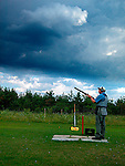 Skeet shooter in approaching storm
