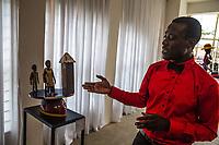 un custode presenta un lavoro di Kifouli Dossou serie Enagnon  rivisatione delle maschere africane