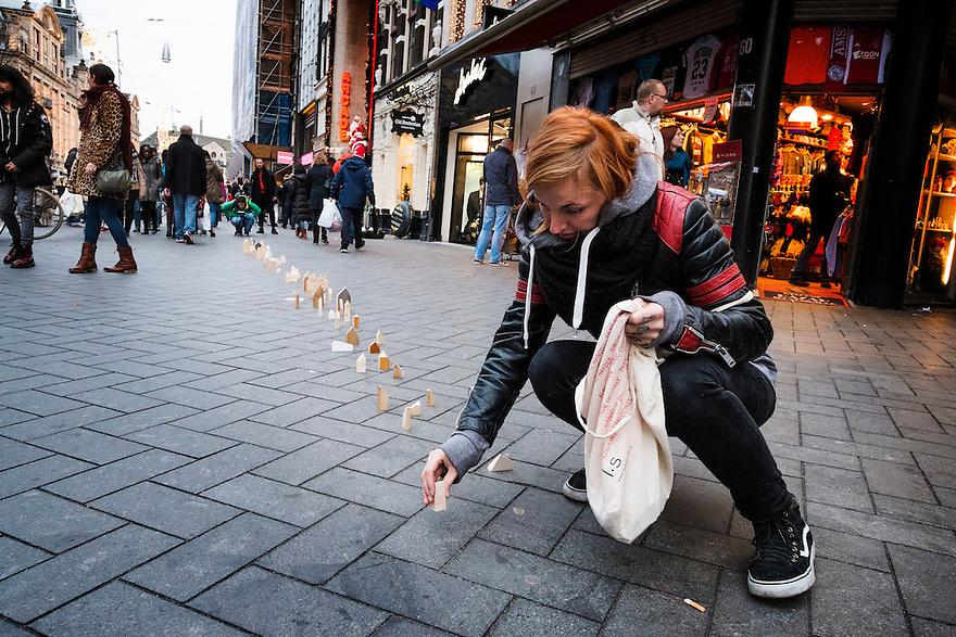 Nederland, Amsterdam, 13 dec 2014<br /> Studente aan kunstacademie zet een kunstwerk neer midden op het voetpad op het damrak. Onverstoorbaar zet zij kleine huisjes van hout neer op het trottoir. Een ander persoon filmt het geheel. <br /> Foto: (c) Michiel Wijnbergh