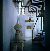 The staircase hall is painted a washed blue with rusty iron stairs leading up to the attic apartment