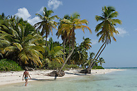 Woman walking by coconuts trees on a pristine beach, Saona Island, Dominican Republic