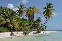Woman walking by coconuts trees on a pristine beach, Saona Island, Dominican Republic