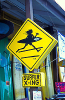 A  humorous Surfer X-ing sign warns drivers to be on the lookout for  northshore surfers.  Sign is posted outside the Surf and Sea store in the historic town of Haleiwa of Oahu's north shore.