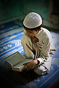 A young religious muslim child is seen learning the Holy Quran by heart in Jamat-ul-Rashad Madrasa in Azamgarh, Uttar Pradesh, India. The Muslim youths are terrified and frightened. Police atrocities are on the rise against the muslim community. Teenagers and young men are picked up without warrants by the UP-ATS from villages of the district Azamgarh, the maligning of boys from a whole district as terrorists. These men may be picked up and implicated in false cases and confessions will be taken out of them through torture.