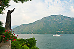 Statue in the gardens of Villa Balbianello, with a view of a ferry boat on Lake Como, Italy