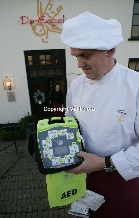 """DODEWAARD - Een defibrillator voor de hele gemeenschap. Met dat doel heeft Inno Venhorst, eigenaar van herberg De Engel in Dodewaard, een AED aangeschaft en vrijdag buiten zijn restaurant opgehangen. Hiermee is hij voorzover bekend het eerste bedrijf dat het hartmassageapparaat niet achter slot en grendel hangt. Collegabedrijven die dat wel doen noemt hij """"egoïstisch"""". De AED is nu 24 uur per dag beschikbaar voor iedereen die het nodig heeft. Het apparaat dat Venhorst heeft aangeschaft is hetzelfde model dat ook in het Witte Huis in Washington hangt. Foto: VidiPhoto"""