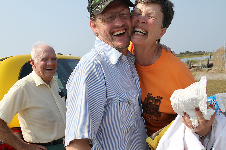 """Celia Meekins, right, hugs friend Bert Dobben, near her husband Roger Meekins, left, at the harbor in Rodanthe, NC, the day after the Meekins survived a house fire in the middle of Hurricane Irene.  """"Happiness is being alive,"""" Celia Meekins later exclaimed.  The Meekins were catching a ferry off of Hatteras Island to the mainland in Stumpy Point, NC, on Monday, Aug. 29, 2011. Photo by Ted Richardson"""