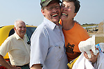 "Celia Meekins, right, hugs friend Bert Dobben, near her husband Roger Meekins, left, at the harbor in Rodanthe, NC, the day after the Meekins survived a house fire in the middle of Hurricane Irene.  ""Happiness is being alive,"" Celia Meekins later exclaimed.  The Meekins were catching a ferry off of Hatteras Island to the mainland in Stumpy Point, NC, on Monday, Aug. 29, 2011. Photo by Ted Richardson"