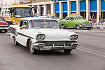 Havana, Cuba; a classic white 1958 Pontiac, serving as a taxi, driving down the Paseo de Marti in Old Havana