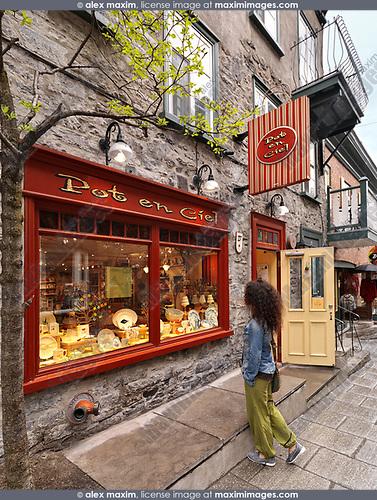 A young woman standing in front of Pot en Ciel store on Rue Petit Champlain historic street in Old Quebec City and looking at its colorful display window, Quebec, Canada. Pot-en-Ciel, Rue du Petit-Champlain, Ville de Québec.