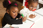 Education preschool 2-4 year olds art activity two girls drawing with markers younger child using a fist grip older girl using a pencil grip tripod grasp younger child talking to self