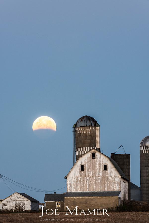 Lunar eclipse over farm buildings near Shakopee, Minnesota.