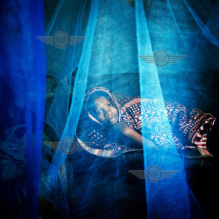 A woman under a mosquito net distributed by the Global Fund on Pemba Island.