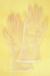 Pair of white nylon ladies see-through gloves lying on antique paper