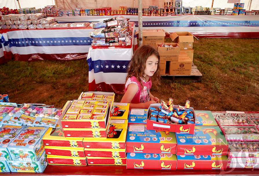 NWA Media/DAVID GOTTSCHALK - 6/23/14 - Addison Shackelford, 5, takes a quick survey of the fireworks at Hale's Fireworks Stand in Farmington Monday June 23, 2014 following a brief rain storm. The stand, which features a variety of fireworks including bottle rockets, mortar shells and family packs, is open from 6:30 a.m. to 12:00 a.m. daily through July 6, 2014.