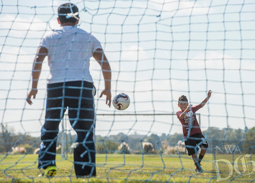 NWA Democrat-Gazette/ANTHONY REYES &bull; @NWATONYR<br /> Tony Sandoval plays with his son Angel Sandoval, 10, Monday, Oct. 17, 2016 at Ward Nail Park in Lowell. Angel is on fall break and his father took the day off work to practice soccer and spend a little time with his son.
