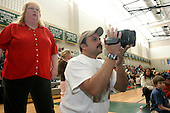 Lisa and Hythem Salem video tape their son Sam in the gym at the Pennridge High School in Perkasie, Pa. during a wrestling match in which twins Jake and Sam compete. The Salem children, 3 sets of twins, are from Russia. Sophia and twin Joseph were adopted at 11 months of age by Hythem and his wife Lisa. The other twins were adopted just 20 months ago. All children are thriving in school and socially. photo by jane therese