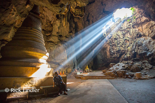 """Photographer: Rick Findler<br /> <br /> THAILAND, Kao Luang: 09 November 2015 An enthralled tourist takes a stroll through Tam Kao Luang """"Cave Kao Luang"""" as the sun shines through a gap. The cave was consecrated to the memory of King Rama IV by his son King Rama V."""