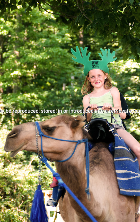 young girl riding a camel