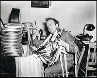 BNPS.co.uk (01202 558833)<br /> Pic:  Juliens/BNPS<br /> <br /> An editing department employee with rolls of film.<br /> <br /> Amazing behind the scenes photos of the classic film Gone With The Wind have come to light 80 years later.<br /> <br /> The comprehensive archive of over 800 images includes candid snaps of the leads Clark Gable and Vivien Leigh unwinding between takes.<br /> <br /> One extraordinary photo shows the pair still in costume playing a board game, with another capturing the burning of Atlanta in the film.<br /> <br /> There is also a picture of the director Victor Fleming holding the novel 'Gone With The Wind' while in discussion with Leigh.