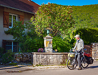Frankreich, Bourgogne-Franche-Comté, Département Jura, bei Arbois (Jura): Radfahrer haelt vor einem Brunnen mit Trinkwasser | France, Bourgogne-Franche-Comté, Département Jura, Arbois (Jura): cyclist stopped in front of a fountain with drinking water