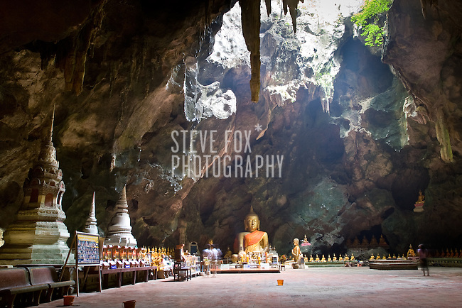 Many Buddha images inside the Tham Khao Luang cave are illiminated by a hole in it's ceiling, Phetchaburi, Thailand.