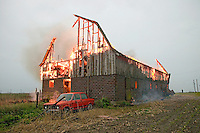 Farmer runs for help as his barn burns from a lightning strike.