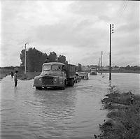 14 septembre 1963. Scène d'inondation : vue d'ensemble camions de la ville de Toulouse escortant plusieurs véhicules à travers les eaux (vue face) ; tout autour campagne inondée.