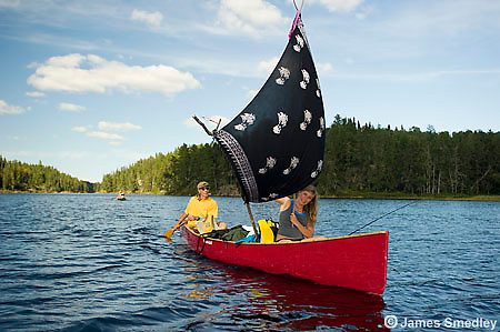 People using an improvised sail on their canoe.