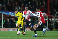 Marcus Brown of Oxford United tries to shake off a challenge from Brentford's Chiedozie Ogbene during Brentford vs Oxford United, Emirates FA Cup Football at Griffin Park on 5th January 2019