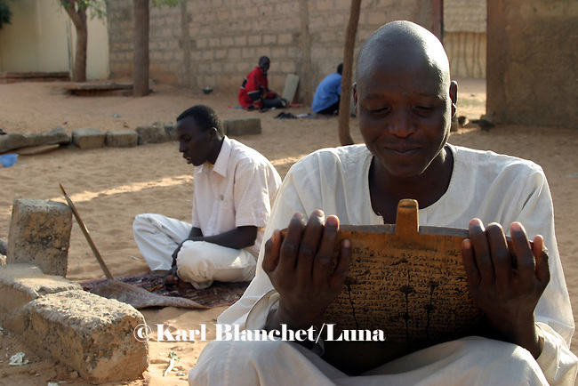 A talibe learning coranic versets written on wooden boards outside the house of the marabout in Maradi, Niger. In Niger, coranic schools still exist and are very traditional. Talibe, pupils, even go and beg for money and food in the afternoon in order to pay the marabout.