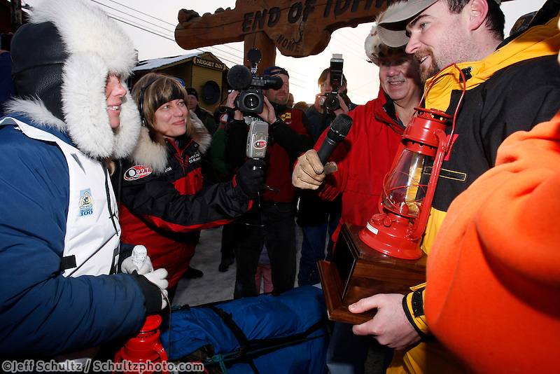 Saturday  March 20, 2010    Rookie musher Celeste Davis recieves her red lantern award from Wells Fargo at the finish line in Nome