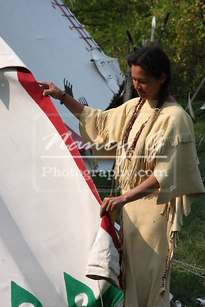 Native American Lakota Indian woman removing tent sides from a tipi