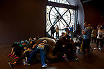 Tourists resting beside the clock at the Musee d'Orsay, Paris.
