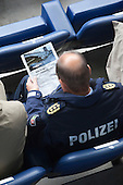 "MSV Arena, Duisburg, North Rhine-Westphalia, Germany - A high-ranking police officer from North Rhine-Westphalia is studying an article from the German mangazine ""Der Spiegel"" during the commemorative service. A commemorative service is held on the 1st anniversary of the Loveparade tragedy in which 21 young people lost their lives and hundreds were injured as they tried to get to the event to celebrate life, love and music; to date, politicians, organisers and police still try to apportion blame, Photo Credit: Bettina Strenske"