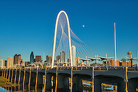Margaret Hunt Hill Bridge with the moon and Continental pedestrian bridge with the Dallas cityscape behind it from across the Trinity river.