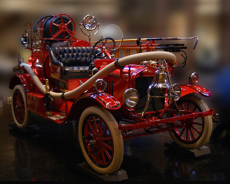 Fully equipped with hose, hooks and bell, this beautiful, eyecatching, red engine with black leather seats and trim and white tires on red wheels, glissens against a blurred background camouflaging the environment at J.K.Lilly III Antique Automoble Museum, Heritage Museum and Gardens, Sandwich, MA.