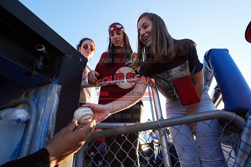 Batavia Muckdogs Rony Cabrera (out of frame) hands a ball to a young fan during a game against the Auburn Doubledays on July 4, 2017 at Dwyer Stadium in Batavia, New York.  Batavia defeated Auburn 3-2.  (Mike Janes/Four Seam Images)