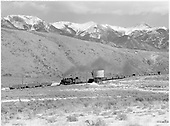 Full-length view of D&amp;RGW narrow gauge freight train passing Round Hill water tank.  Hills and Sangre de Cristo mountains behind.<br /> D&amp;RGW  Round Hill, CO  Taken by Richardson, Robert W. - 2/16/1950