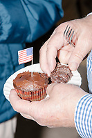 A man holds a chocolate cupcake decorated with American flags are seen on a table at the Milford Democrats' Potluck Supper at the Unitarian Universalist Congregation Church in Milford, New Hampshire, USA, on Sat., Apr. 6, 2019. Democratic presidential candidate and Congressional Representative Eric Swalwell (D-CA 15th) spoke at the event. Swalwell is running primarily on gun control issues.
