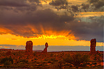 Colorful sun rays under the clouds at sunset at Balanced Rock in Arches National Park near Moab, Utah, USA.