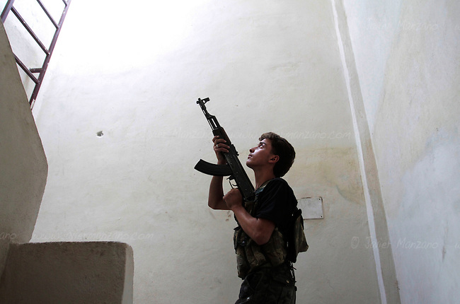 A young Free Syria Army soldier helps secure a building in the Amariya front of Aleppo.