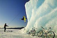 Ice climbers tackle an iceberg frozen in Mendenhall Lake, Juneau, Alaska in the Tongass National Forest. (Southeast Alaska). They crossed the frozen lake on bicycles. Juneau Alaska, Mendenhall Lake, Tongass National Forest.